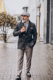 Uomo bello anziano che beve caffè fuori strada outside