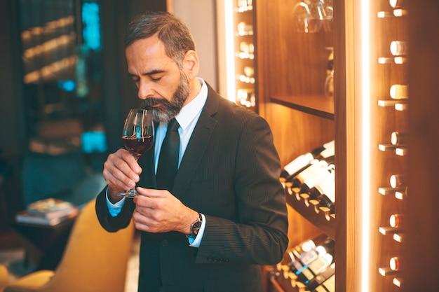 Uomo bello senior che beve vino rosso