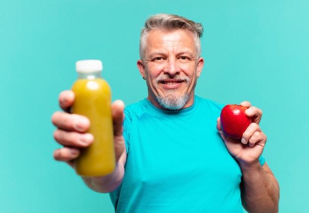 Un bell'uomo anziano che beve un frullato vegano