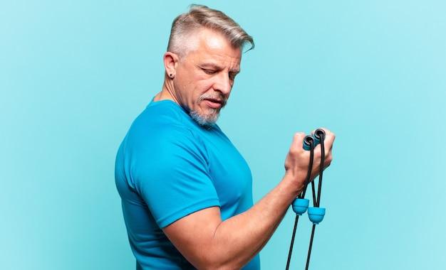 Uomo anziano bello che pratica fitness e indossa abiti sportivi