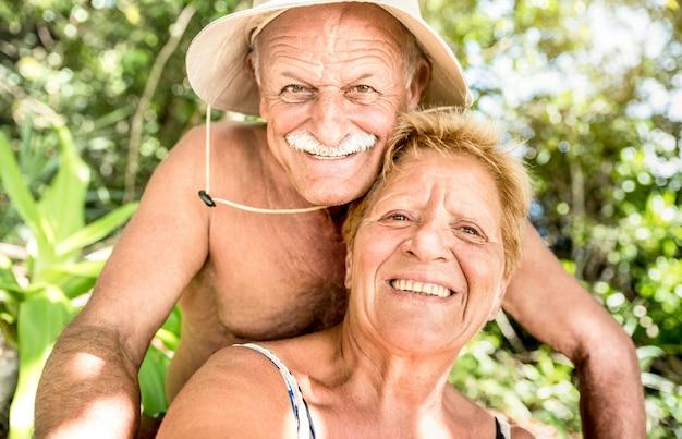 Coppie felici senior divertendosi prendendo selfie al viaggio nella giungla della tailandia durante il giro saltellante dell'isola