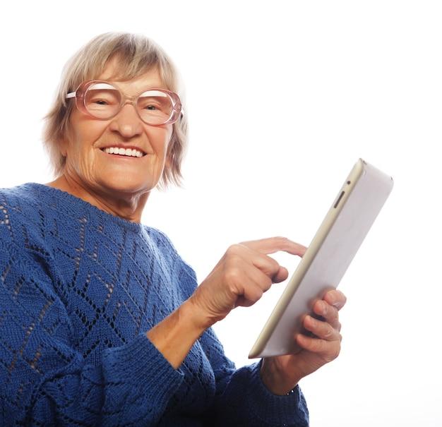 Senior donna felice utilizzando ipad isolato su sfondo bianco