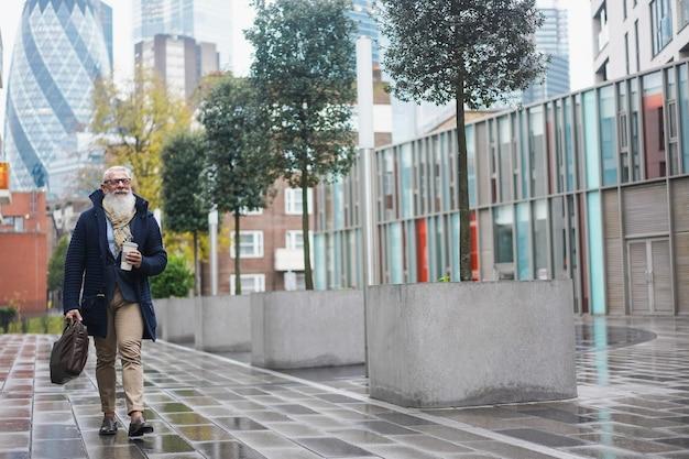 Uomo anziano di affari dei pantaloni a vita bassa che cammina per lavorare sulla città