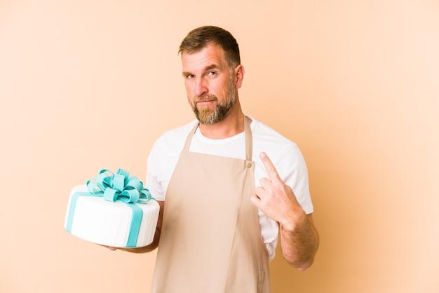 Anziano che tiene una torta isolata sul beige che punta con il dito contro di te come se invitando ad avvicinarsi.