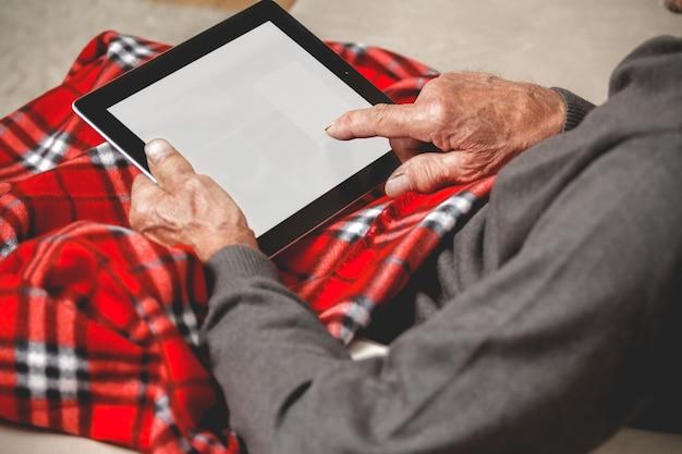 Senior tenendo una tavoletta in mano