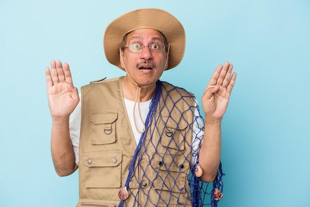 Senior pescatore indiano tenendo la rete isolata su sfondo blu sorpreso e scioccato.