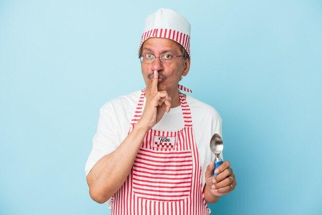 Anziano gelato indiano che tiene una paletta isolata su sfondo blu mantenendo un segreto o chiedendo silenzio.