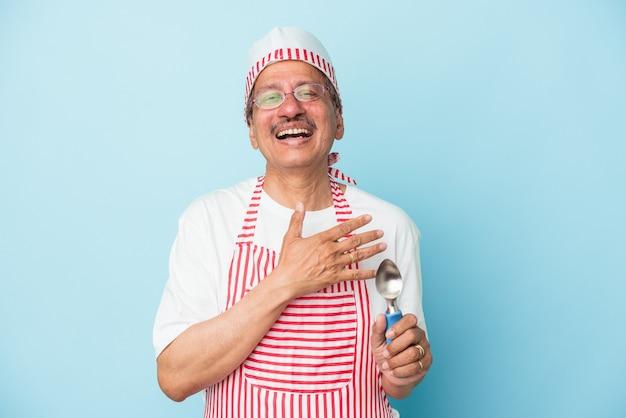 Senior indian gelatiere tenendo una paletta isolato su sfondo blu ride ad alta voce tenendo la mano sul petto.