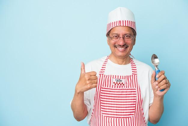 Uomo gelato indiano senior che tiene una paletta isolata su fondo blu che sorride e che alza pollice su