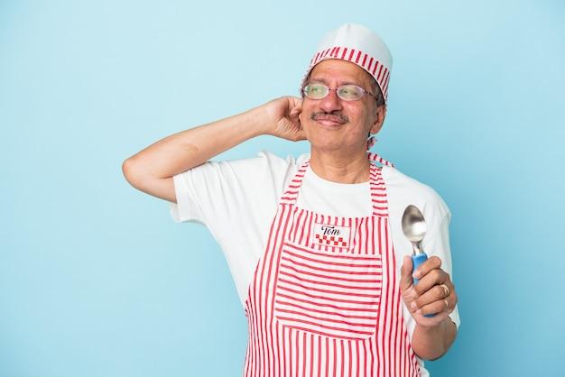 Uomo gelato indiano senior che tiene una paletta isolata su fondo blu che tocca la parte posteriore della testa, pensando e facendo una scelta.