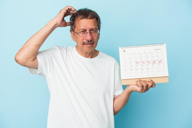 Uomo indiano anziano che tiene un calendario isolato su sfondo blu scioccato, ha ricordato un incontro importante.