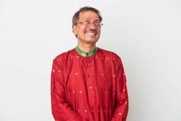 Senior uomo indiano che indossa un costume indiano isolato su sfondo bianco sognando di raggiungere obiettivi e scopi