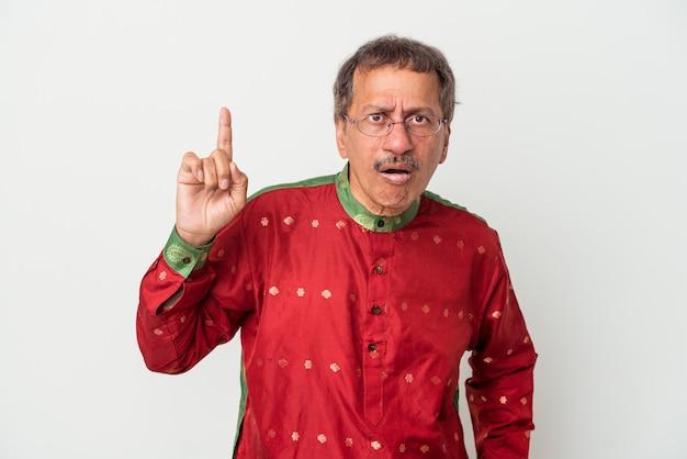 Uomo indiano anziano che indossa un costume indiano isolato su sfondo bianco avente un'idea, concetto di ispirazione.