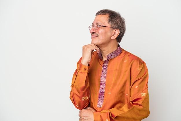 Senior uomo indiano che indossa un costume indiano isolato su sfondo bianco guardando lateralmente con espressione dubbiosa e scettica.