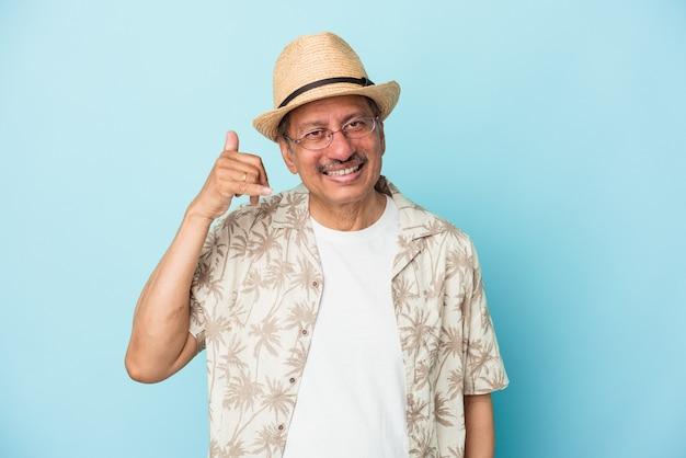 Senior uomo indiano che indossa abiti estivi isolati su sfondo blu senior donna indiana che indossa un costume africano isolato su sfondo bianco che mostra un gesto di chiamata di telefonia mobile con le dita.