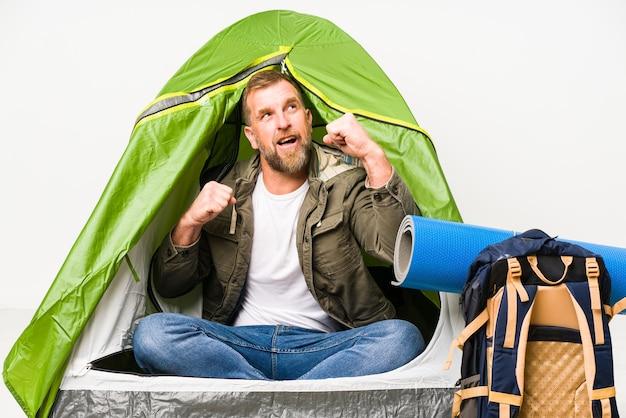 Anziano all'interno di una tenda isolata sul pugno di sollevamento bianco dopo una vittoria, concetto del vincitore.