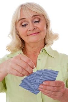 Carte da gioco della signora anziana. allegra donna anziana che tiene in mano le carte da gioco e sorride mentre sta in piedi isolata su sfondo bianco