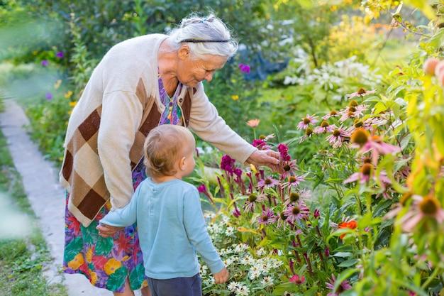 Signora maggiore che gioca con il ragazzino nel giardino fiorito. nonna con nipote guardando e ammirando i fiori in estate. bambini che fanno giardinaggio con i nonni. bisnonna e pronipote.