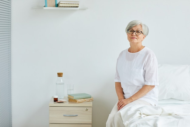 Signora senior che indossa abiti bianchi seduto sul letto nella stanza del reparto ospedaliero