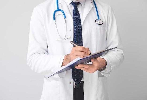 Senior medico maschio con appunti su sfondo grigio su sfondo grigio, primo piano