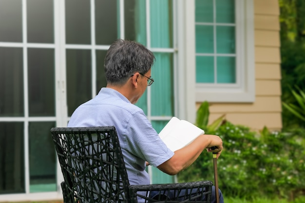 Maschio anziano che legge e si rilassa in cortile