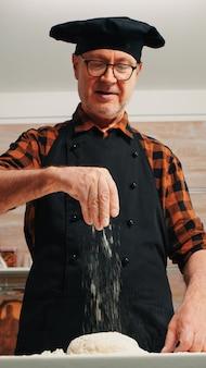 Senior uomo l'aggiunta di farina sulla pasta a mano guardando sorridente della fotocamera. chef anziano in pensione con bonete e spolverata uniforme, setacciatura diffusione rew ingredienti con cottura a mano pizza e pane fatti in casa