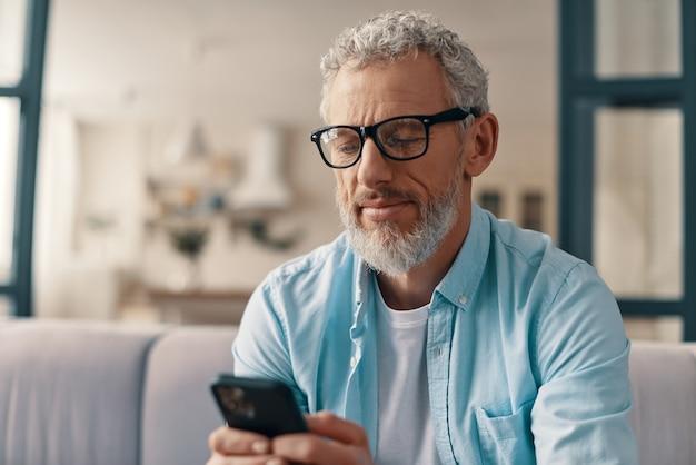 Uomo anziano in abbigliamento casual e occhiali che manda un sms a qualcuno che usa uno smartphone mentre è seduto sul divano di casa