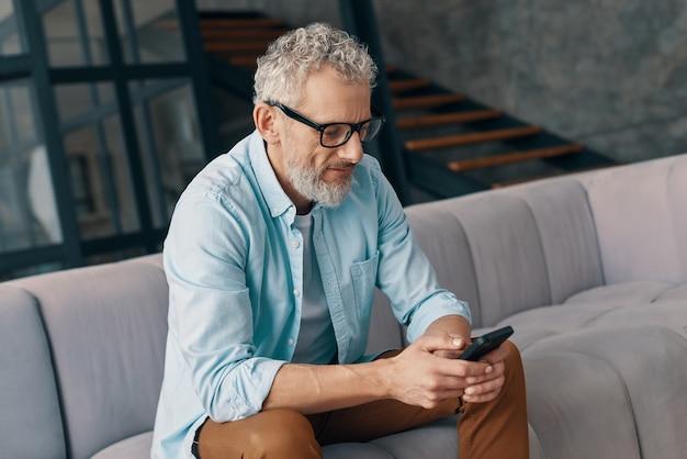Uomo anziano in abbigliamento casual e occhiali che utilizza uno smartphone mentre è seduto sul divano di casa