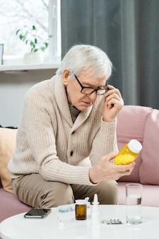 Uomo anziano in abbigliamento casual e occhiali seduto sul divano in soggiorno, tenendo una bottiglia di pillole sul tavolo e leggendo contiene compresse