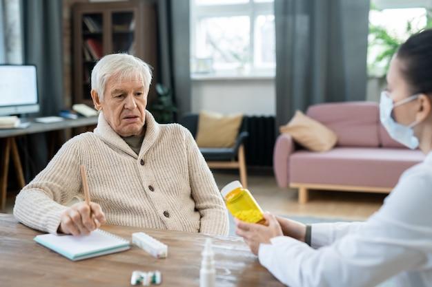 Uomo anziano in abbigliamento casual guardando una bottiglia di pillole nelle mani di una giovane dottoressa seduta al tavolo di fronte a lui e dando consigli