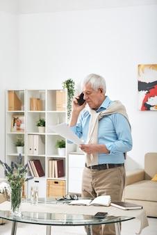 Uomo anziano in abbigliamento casual guardando attraverso documenti finanziari e parlando su smartphone mentre è in piedi al tavolo a casa