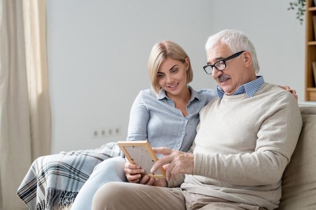 Uomo anziano in abbigliamento casual che punta alla foto nel telaio mentre ne discute con la sua giovane figlia bionda graziosa a casa