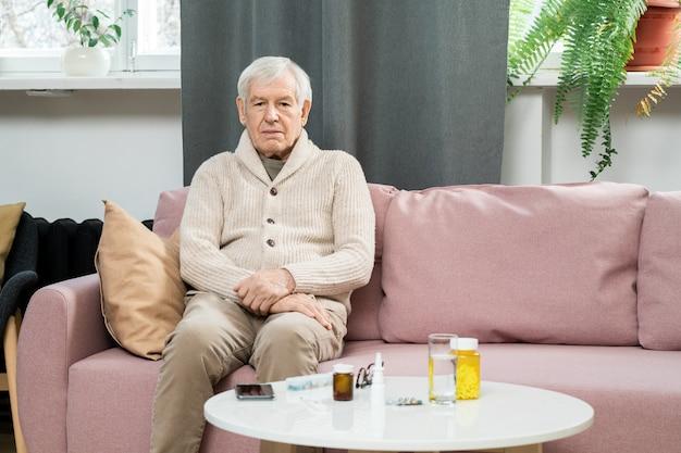 Uomo anziano in abbigliamento casual seduto sul divano vicino a un tavolino con pillole e bicchiere d'acqua e in attesa del medico contro le finestre nel soggiorno