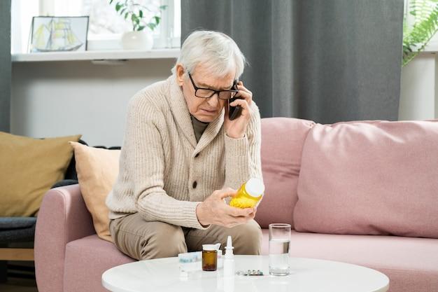 Uomo anziano in abbigliamento casual seduto sul divano, tenendo in mano una bottiglia di pillole e consultando il suo medico sullo smartphone contro le finestre del soggiorno