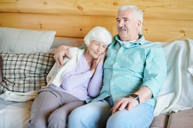 Uomo anziano in abbigliamento casual seduto sul divano e guardare il programma tv mentre sua moglie sonnecchia al suo fianco la sera