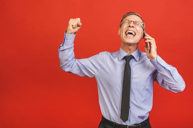 Uomo senior che celebra pazzo e stupito per il successo con le braccia alzate e gli occhi aperti che urla eccitato. concetto di vincitore. usando il telefono.