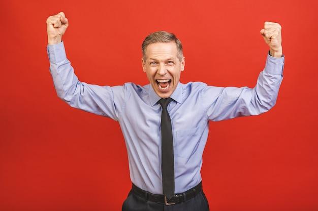 Uomo senior che celebra pazzo e stupito per il successo con le braccia alzate e gli occhi aperti che urla eccitato. concetto di vincitore.