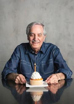 Uomo anziano che festeggia con un cupcake di compleanno