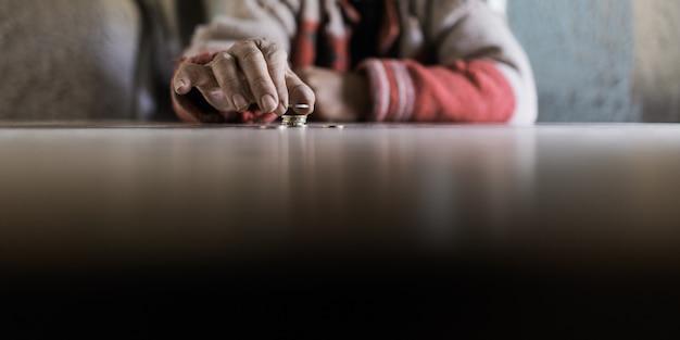 Uomo maggiore che conta le sue ultime monete in euro in un'immagine concettuale di mancanza e povertà.