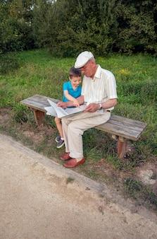 Uomo anziano e bambino carino che leggono un giornale seduti su una panchina del parco. due diverse generazioni concetto.