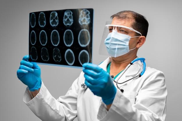Senior uomo medico in maschera esamina la testa mri in ospedale da vicino