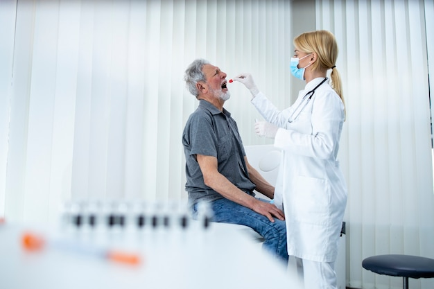 Uomo maggiore che fa il test pcr presso l'ufficio dei medici durante l'epidemia di coronavirus