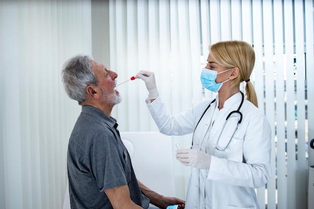 Uomo maggiore che fa la prova di gola di pcr all'ufficio dei medici durante l'epidemia di virus della corona