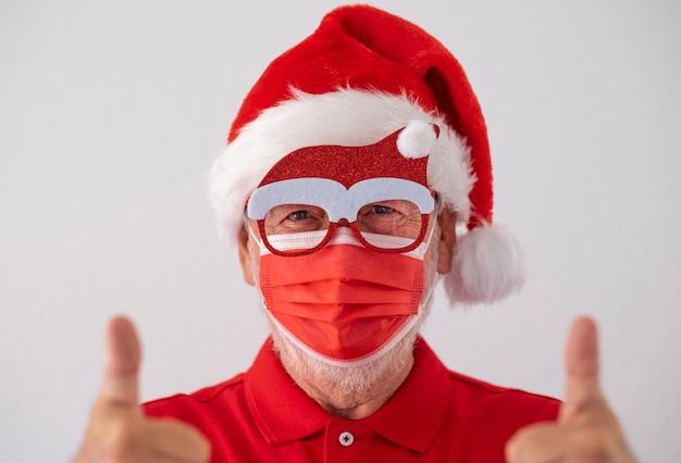 Un uomo anziano vestito di rosso da babbo natale che indossa una maschera chirurgica a causa del coronavirus e fa segno di ottimismo. buon natale ai tempi del virus covid-19.