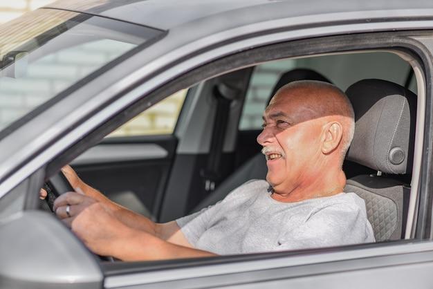 Uomo anziano alla guida di un'auto, guardando la strada. concetto di guida.