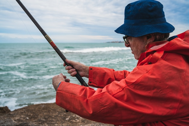 Uomo maggiore che pesca in mare.