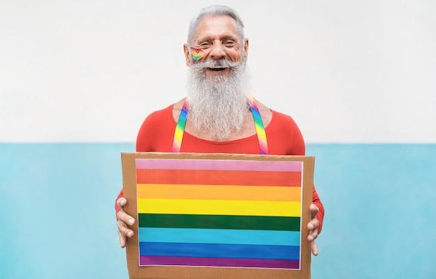 Uomo anziano al gay pride che tiene bandiera arcobaleno lgbt