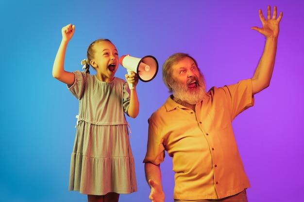 Uomo anziano e nipote su sfondo al neon