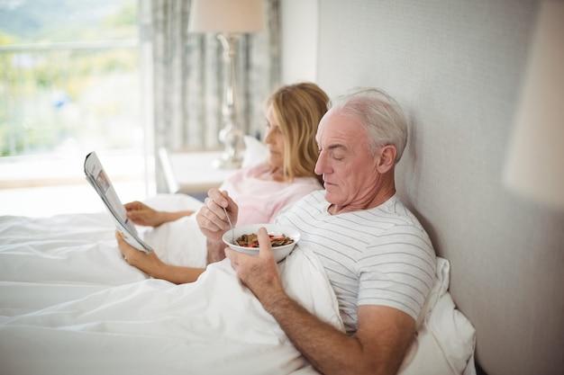 Uomo maggiore che mangia colazione a letto