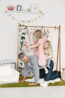 Uomo anziano che si diverte con le sue nipoti. interno di casa.